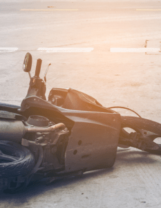 Photo of a crashed motorcycle in the middle of the road.