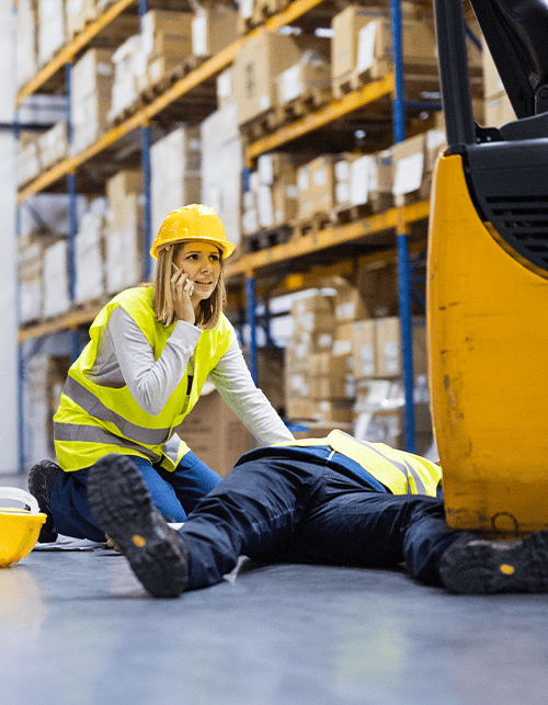 Photo of a female construction worker calling for help sitting beside an injured co-worker